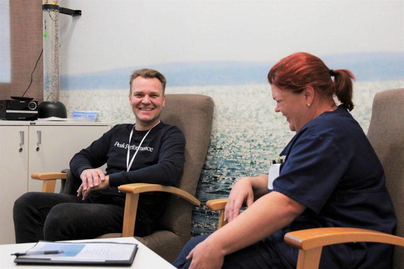 Mies ja nainen istuvat hymyilevinä taukohuoneessa.