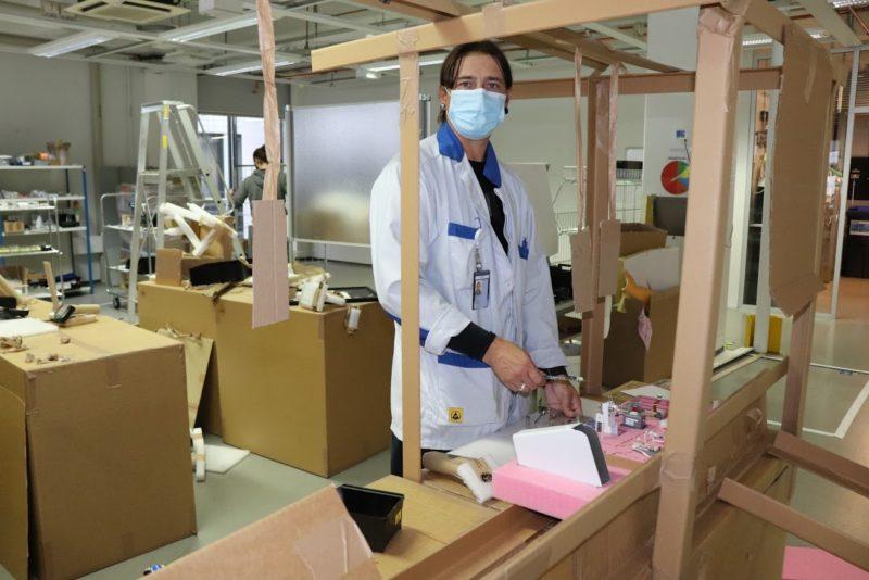Mies suu-nenäsuojaimessa seisoo pahvista rakennetun tuotantolinjamallinnoksen ääressä.