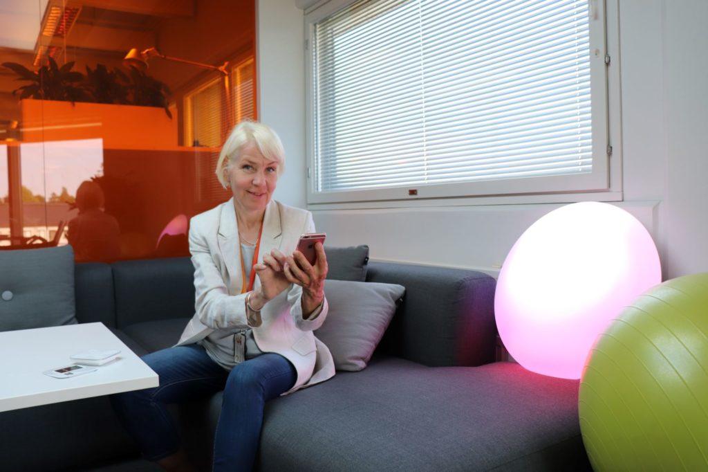 Valaistussuunnittelija Sara Leino istuu työpaikkansa taukotilassa sohvalla. Kuvassa hän pitää kännykkäänsä, jolla hän ohjaa pyöreän valaisimen värisävyä.