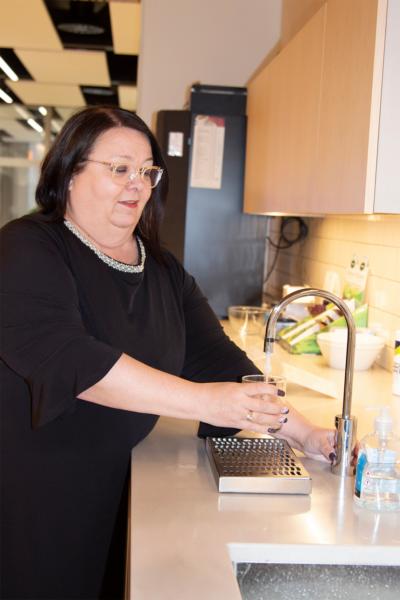 Nainen seisoo pöydän ääressä työpaikan taukotilassa. Hän laskee vettä lasiin automaatista.