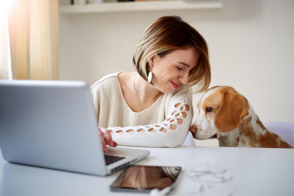 Tietokoneen ääressä istuva nainen kumartuu kohti vieressä istuvaa koiraa.