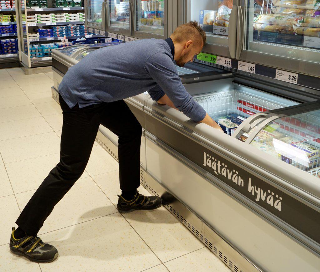 Nuori mies täyttää myymälässä pakastinta.
