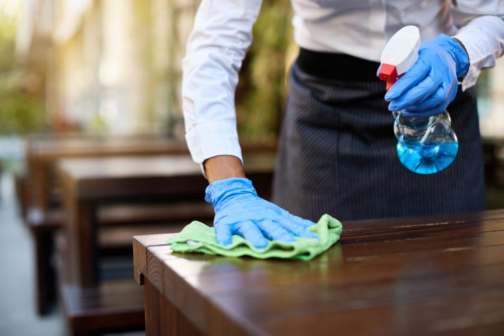 Tarjoilija pyyhkii pöytää suihkepullo kädessään. Hänestä näkyy vain käsi ja lantionseutu.