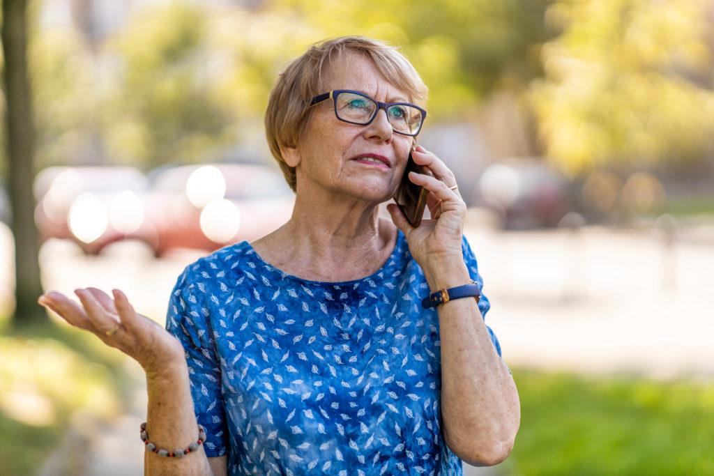 Ikääntynyt nainen seisoo ulkona kännykkä korvallaan kuunnellen.