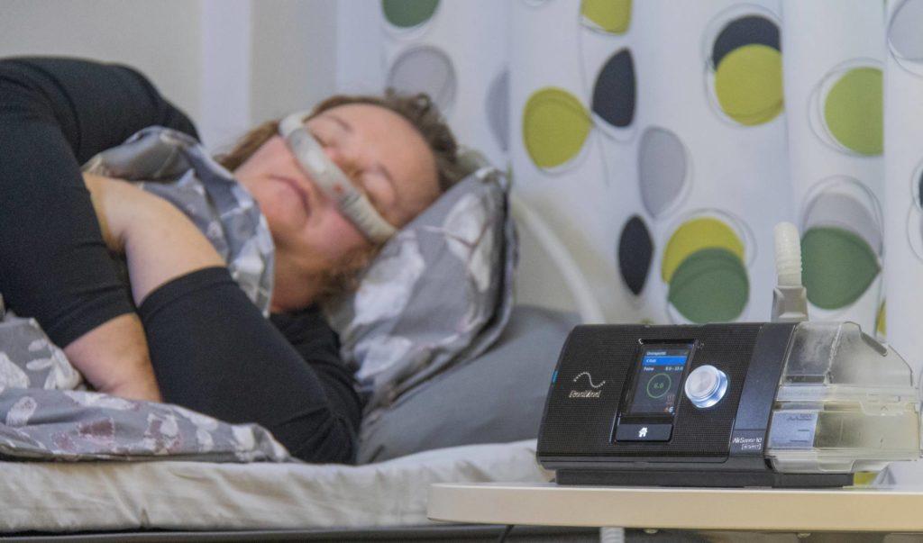 Nainen nukkuu ylipainelaite naamallaan.
