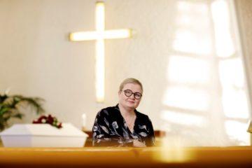 Vaalea, silmälasipäinen nainen istuu kauniissa kappelissa takanaan valaiseva risti.