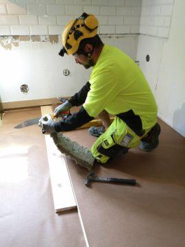 Mies on kumartuneena työhön. Hän käyttää karhunvillaan leikkaamisessa terää.