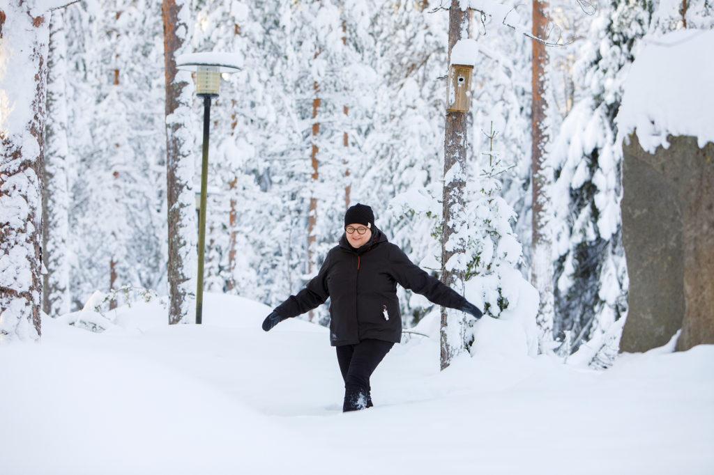 Nainen kävelee mäntykankaalla lumisessa maastossa. Puussa näkyy linnunpönttö.